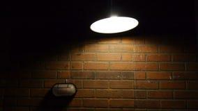 向高处发射样式在摇摆的边转动的云幂灯支持 摄制与在砖墙背景的演播室光 灯 影视素材