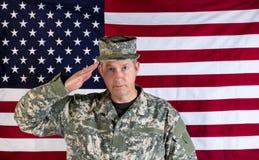 向致敬与美国旗子的男性经验丰富的solider在背景中 免版税库存图片