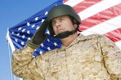 向致敬在美国国旗前面的确信的战士 免版税库存照片
