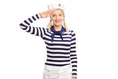 向致敬往照相机的年轻女性水手 免版税库存照片