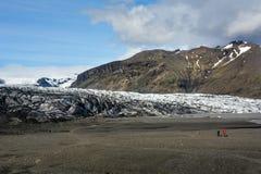 向Skaftafellsjokull冰川的岩石道路与无法认出的少量 免版税库存图片
