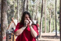 吟呦诗人-重建`北欧海盗村庄`的参加者在本Shemen附近演奏在阵营的口琴在森林里在Isr 免版税库存图片