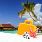 含沙和手提箱前面的组合与被弄脏的热带海岛 免版税库存照片