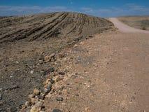 含沙旅行纹理通过与分裂的石头的纳米比亚沙漠背景干多灰尘的岩石山风景地面  库存图片