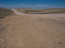 含沙旅行Copyspace通过与分裂的石头a的纳米比亚沙漠背景干多灰尘的岩石山风景地面  免版税库存照片