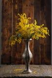 含羞草花束在一个美丽的花瓶的在木背景 免版税库存照片