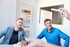 听一个同事` s介绍的微笑的商人在办公室 免版税库存照片