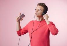 听一年轻的帅哥的画象有耳机的与智能手机的音乐 库存照片