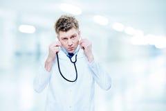 听与听诊器的英俊的医生 图库摄影