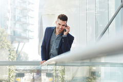 听与手机的微笑的年轻商人 免版税库存图片