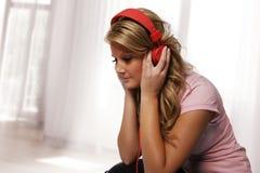 听与耳机的女孩 免版税库存照片