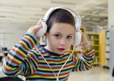 听与耳机的孩子 免版税库存照片