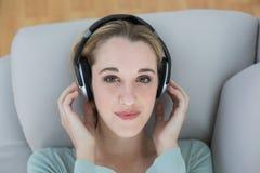 听与耳机的美丽的偶然妇女到说谎在长沙发的音乐 免版税图库摄影