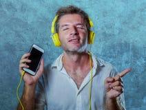 听与黄色耳机的音乐歌曲的年轻可爱和愉快的凉快的人使用互联网在恍惚s的手机跳舞 库存照片