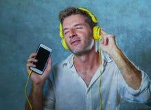 听与黄色耳机的音乐歌曲的年轻可爱和愉快的凉快的人使用互联网在恍惚s的手机跳舞 免版税库存照片