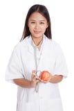 听与stethosco的一个苹果的年轻亚裔女性医生 免版税库存照片