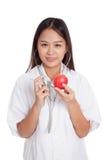 听与stethosco的一个苹果的年轻亚裔女性医生 库存图片