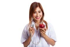 听与stethosco的一个苹果的年轻亚裔女性医生 库存照片