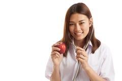 听与stethosco的一个苹果的年轻亚裔女性医生 免版税库存图片