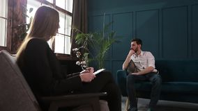 听人客户的女性心理学家坐在蓝色办公室内部的心理会议期间 影视素材