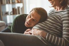 听他的未出生的孩子的激动的人通过女性腹部 免版税库存照片