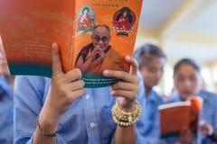 听他的神圣的西藏学生14达赖喇嘛Tenzin给在他的住所的Gyatso教学在达兰萨拉,印度 免版税图库摄影