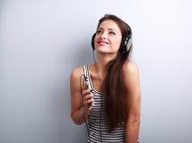 听俏丽的微笑的女孩音乐佩带的耳机holdi 免版税库存图片
