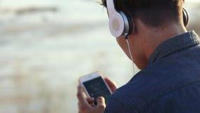 听到与他的耳机的音乐的一个十几岁的男孩的特写镜头英尺长度 股票视频