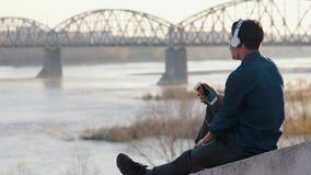 听到与他的耳机的音乐的亚裔mixed-race深色的十几岁的男孩 股票录像