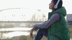 听到与她的耳机的音乐的亚裔mixed-race深色的十几岁的女孩 影视素材
