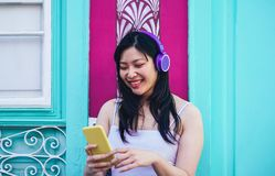 听到与室外的耳机的音乐的愉快的亚裔女孩-演奏她喜爱的播放表音乐的年轻中国妇女 免版税图库摄影