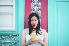 听到与室外的耳机的音乐的愉快的亚裔女孩-演奏她喜爱的播放表音乐的年轻中国妇女 图库摄影