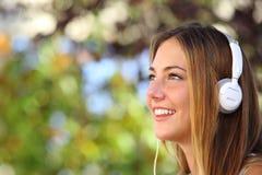 听到与室外的耳机的音乐的美丽的妇女 库存图片