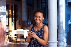 听到与巧妙的电话和耳机的音乐的愉快的年轻黑人妇女 免版税图库摄影