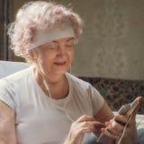 听到与微笑的音乐的womElderly老人妇女 在fitnessan听的休息到与微笑的音乐以后 在健身以后的休息 库存图片