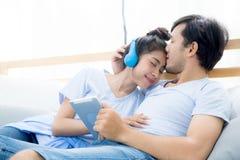 听到与片剂的音乐的美好的亚洲年轻夫妇 免版税库存图片