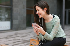 听到与电话的音乐的年轻美丽的妇女户外 库存照片