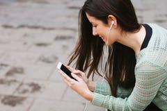 听到与电话的音乐的年轻美丽的妇女户外 免版税库存照片