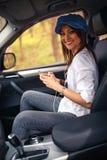 听到与移动汽车的耳机的音乐的女孩 免版税库存图片