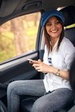 听到与移动汽车的耳机的音乐的妇女 库存图片