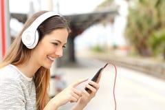 听到与等待火车的耳机的音乐的青少年的女孩 库存照片
