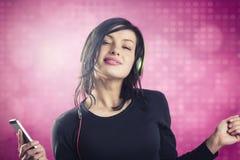 听到与耳机和跳舞的音乐的微笑的女孩 图库摄影