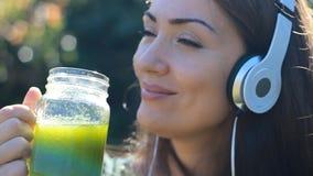 听到与耳机和饮用的绿色圆滑的人的音乐的美丽的妇女室外在一个晴朗的夏日 影视素材
