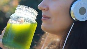 听到与耳机和饮用的绿色圆滑的人的音乐的美丽的妇女 股票录像