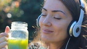 听到与耳机和饮用的绿色圆滑的人的音乐的美丽的妇女 股票视频