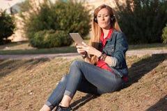 听到与耳机和smartp的音乐的年轻现代妇女 免版税库存照片