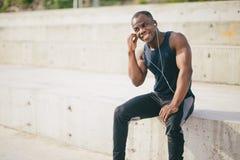 听到与耳机的冥想的音乐的年轻慢跑者 库存图片