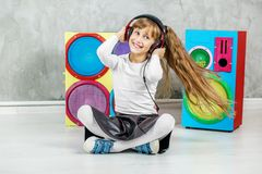 听到与耳机的收音机的美丽的小女孩和 库存图片