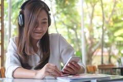 听到与耳机的音乐和拿着有感到的亚裔妇女巧妙的电话愉快和在现代咖啡馆放松 免版税库存照片