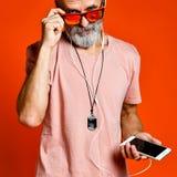 听到与耳机的音乐的一个年长人的图象 免版税库存照片